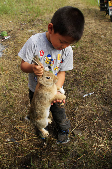 A boy is holding his wild rabbit, Beijing Hikers Hailar, July014, 2011